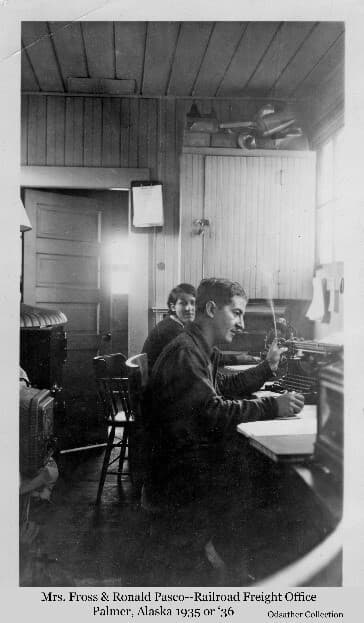 Image shows a woman and man, identified as Mrs, Fross and Ronald Pasco, in the Railroad freight office in Palmer.