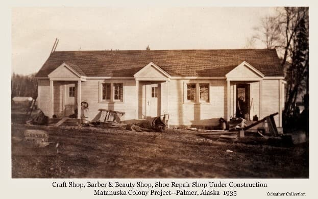 Image shows the west side of the building that initially housed the craft shop, barber and beauty shop, and the shoe repair shop, with exterior construction near completion. A man working in one doorway is visible. The shop spaces would go on to house other functions over the years.