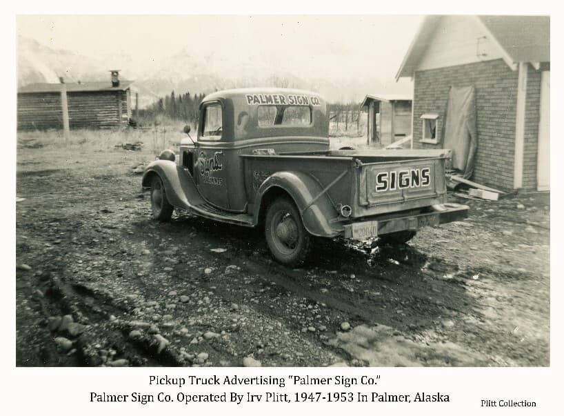 Image shows a pick-up truck with words painted on the cab, side door and tail gate advertising signs and the Palmer Sign Co. Three buildings are partially visible in middle ground with forest and mountains faintly visible beyond.