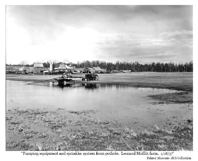 "Image shows a grass field with a pond in foreground. A farm tractor, pump and pipes are at the edge of the pond. A man attends the tractor with a pickup truck behind. A collection of barns, houses, silos, and Quonset huts are in background at the edge of the forest. Caption: ""Pumping equipment and sprinkler system from pothole. Leonard Moffitt farm."""