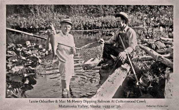 """Image shows two men, identified as Louis Odsather and Mac McHenry, dip netting at Cottonwood Creek. Louis Odsather is standing in the water of Cottonwood Creek in his shorts holding up a salmon in one hand and supporting a pole-and-chicken-wire dip net with a salmon in it. """"Mac"""" McHenry is seated on the stream bank with one hand supporting the dip net basket. Lilly pad plants and logs are seen in foreground with meadow vegetation and trees on the far side of the creek."""