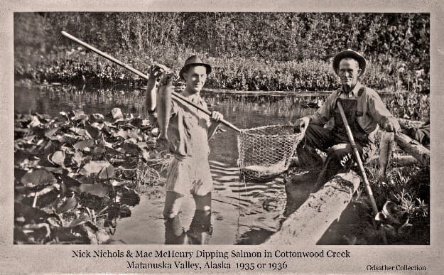 """Image shows two men, identified as Nick Nichols and Mac McHenry, Dip netting in Cottonwood Creek. """"Nick"""" Nichols is standing in the water of Cottonwood Creek in his shorts holding up a salmon in one hand and supporting a pole-and-chicken-wire dip net with a salmon in it. """"Mac"""" McHenry is seated on the stream bank with one hand supporting the dip net basket. Lilly pad plants and logs are seen in foreground with meadow vegetation and trees on the far side of the creek."""
