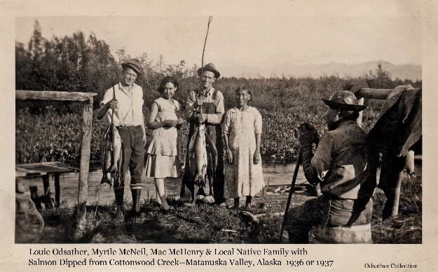 """Image shows four people standing on the bank of Cottonwood Creek facing the camera and one man seated facing away. Standing on the left is Louis Odsather holding a string of Salmon. Next is a young native girl identified as Myrtle McNeil. Next is """"Mac"""" McHenry holding a string of salmon, and to his left is an unidentified older native woman. A native man sits on a wooden keg at the right of the photo. A fish cleaning table and wooden pole racks are nearby. Cottonwood Creek is evident behind the people with meadow vegetation and trees on the far side of the creek and mountains in the far background."""