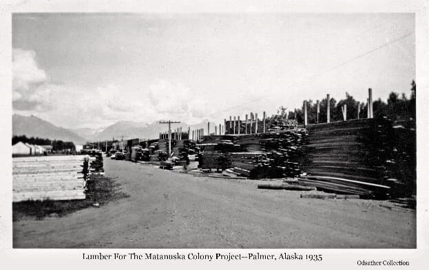 Image shows lumber stacked alongside both sides of a street with rail cars behind stacks to the right. A power pole supports power lines paralleling the rail cars. Tents are visible in near background with mountains beyond.