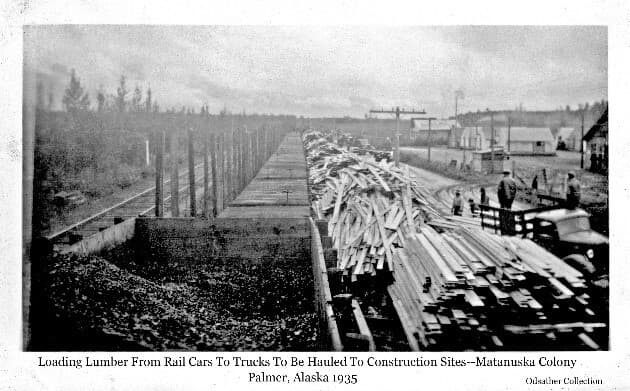 Image is a view from atop a railroad car looking along the train at several empty flatcars with unloaded lumber stacked alongside. Several trucks and men are visible on the street parallel to the lumber stacks preparing to load and haul the lumber away. A vacant set of railroad tracks is on the left. Power poles and lines are evident along the street. Tents and other buildings are visible in middle ground to the right.