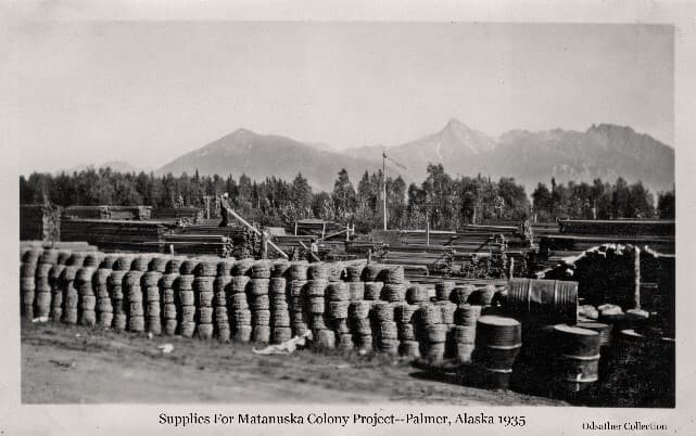 Image is an easterly view including many rolls of wire and steel barrels stacked in the foreground, stacks of lumber behind with two men visible moving boards. Heavy forest is beyond with mountains in the background.