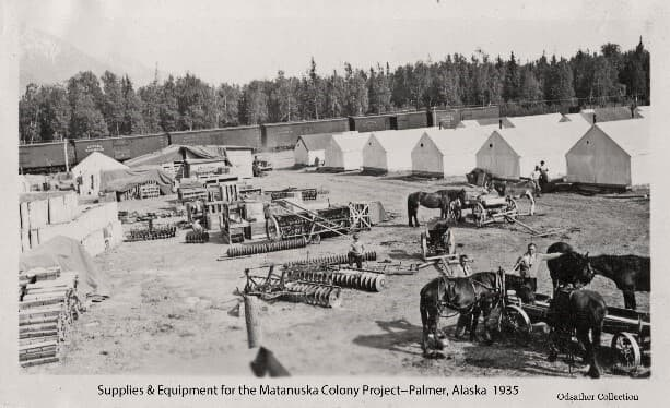Image is a low oblique view looking across a yard containing various farm equipment, horses and people with a line of railroad boxcars behind. Numerous tents and tarp-covered crates are evident. Heavy forest forms the backdrop with a mountain beyond.