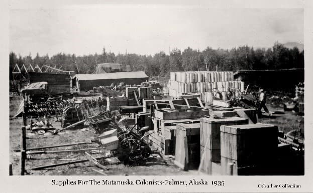 Image is a low oblique view looking across a yard containing various farm equipment and supplies. Several men are visible and various small buildings. Heavy forest forms the backdrop with a mountain beyond.