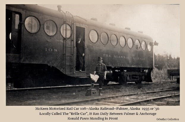 """Image shows the McKeen Motorized Rail Car, locally called the """"Brill Car"""" or """"Brill Train"""", on the Palmer siding. Ron Pasco, station freight agent, stands in front and another man stands in the car's doorway. This car ran daily between Palmer and Anchorage for several years, hauling passengers and freight."""