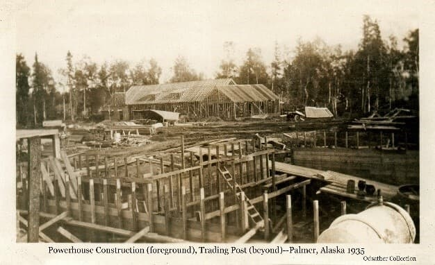 Image shows Powerhouse basement form framing in the foreground and the Trading Post building with framing largely complete in the background. A saw shed is visible in front of the Trading post and construction materials are scattered about. Trees form the backdrop behind the Trading Post.