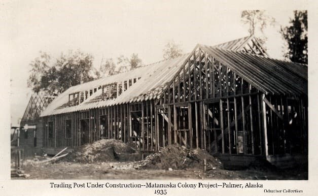 Image shows the north side of the new Trading Post building under construction with framing largely in place. Piles of dirt are in foreground, trees behind the building.