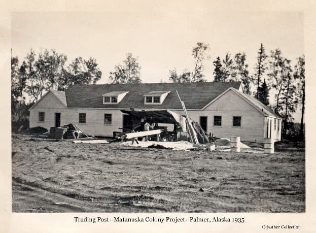 Image shows the north side of the new Trading Post building with exterior construction largely complete. A saw shed with a man working in it is seen in front of the building. Lumber and other building materials are nearby. Soft ground is in foreground, trees beyond.