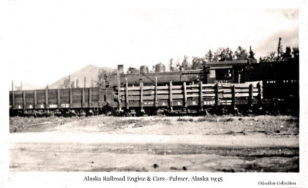 Image shows two open rail freight cars on one set of tracks with a train engine on tracks behind the cars. Location is at the Palmer siding, the empty cars having delivered material to the Matanuska Colony project. Lazy Mountains is visible in background.