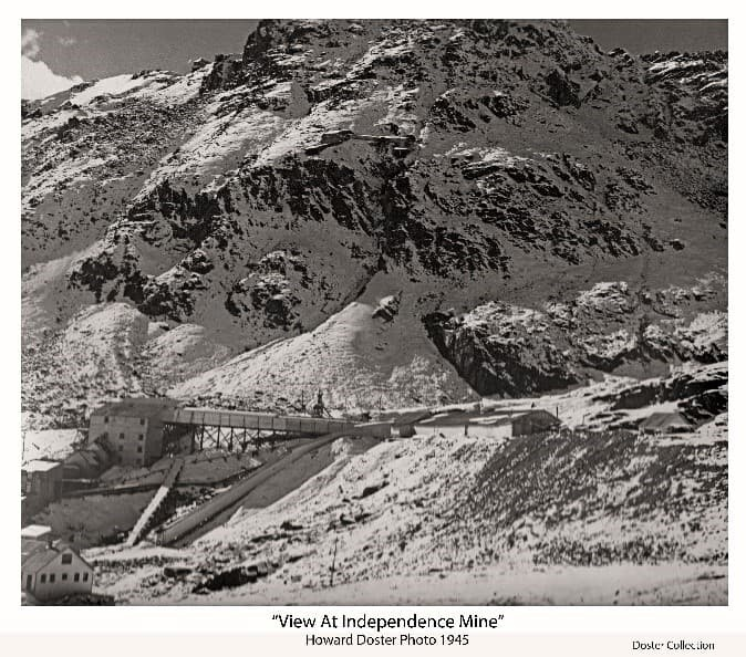 Image is a major portion of the larger print showing tailing dumps, buildings, covered stairways and corridors, and other structures of the Independence Gold Mine facility in its rugged mountainous environment as it appeared in 1945.