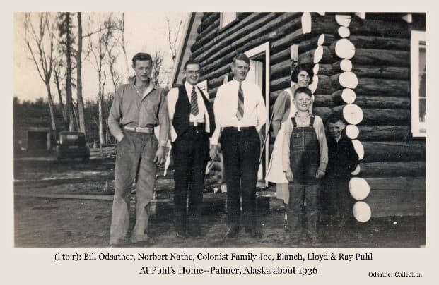 Image shows six people, identified from left as Bill Odsather, Norbert Nathe, Joseph Puhl, Blanch Puhl, Lloyd Puhl, and Ray Puhl, standing in front of the Puhl Colony home. The house is of logs with their ends painted white. A pickup truck is visible in background.