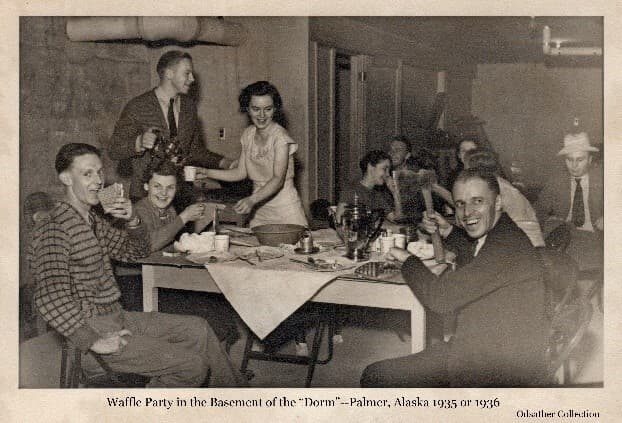"""Image shows a group of young men and women in the basement of the Colony """"Dorm"""" enjoying a meal including waffles and coffee."""