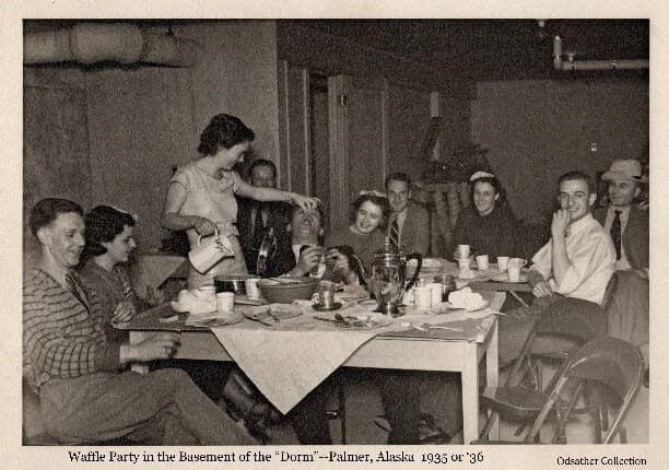 """Image shows a group of young men and women in the basement of the Colony """"Dorm"""" enjoying a meal including waffles and coffee. Most of the people were ARRC employees."""