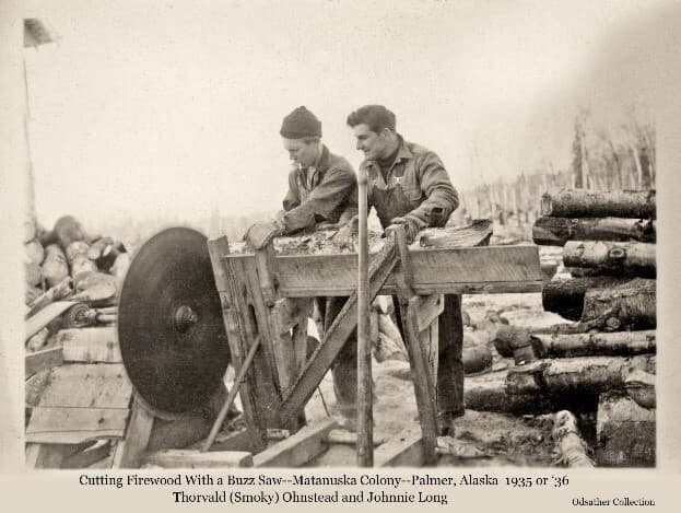 Image shows two men, identified as Thorvald (Smoky) Ohnstead on the left and Johnnie Long on the right, cutting firewood with a stationary buzz saw. Logs to be cut are stacked on the right. They are holding a log in the cradle, pushing it into the circular saw blade at left. The belt turning the blade is visible at the far left.