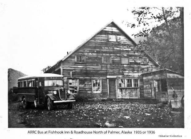 Image shows the end view of a large two story wooden building with peaked roof and smaller shed roofed building adjacent. A bus is parked adjacent to the large building. Mountains are evident in the near background.