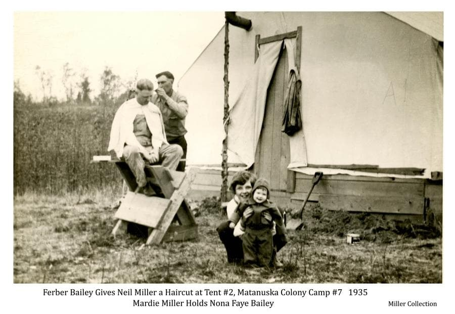 Image shows a man, identified as colonist Neil Miller, sitting on a saw buck in front of a colony tent while another man, identified as colonist Ferber Bailey, cuts his hair.  A young girl, identified as Mardie Miller, holds a smaller child, identified as Nona Faye Bailey, in foreground.  The tent is identified as tent #2 at temporary Camp 7.