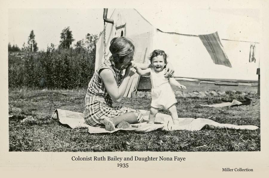 Image shows a woman, identified as colonist Ruth Bailey, sitting on a blanket with her daughter, Nona Faye, in front of a colony tent, identified as tent #2 at temporary camp 7.