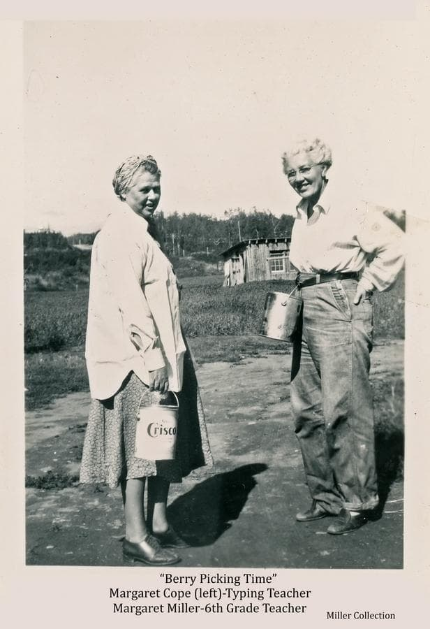 Image shows two women, identified as Margaret Cope (left), Palmer school typing teacher, and Margaret Miller, Palmer 6th grade teacher, ready to begin berry picking with berry buckets at hand.  A log chicken coop is behind them in middle ground with forest beyond.  A road and power line appear faintly among the trees.