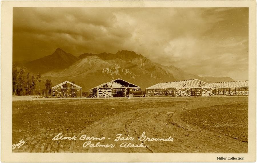 Image is an easterly view across the race track in foreground to four unfinished frame structures identified as stock barns.  A car is parked in front of one of the barns.  A small group of spruce trees is at left.  Mountains are prominent in background under cloudy skies.  A note on the reverse indicates that the barns were covered with tarps when used.