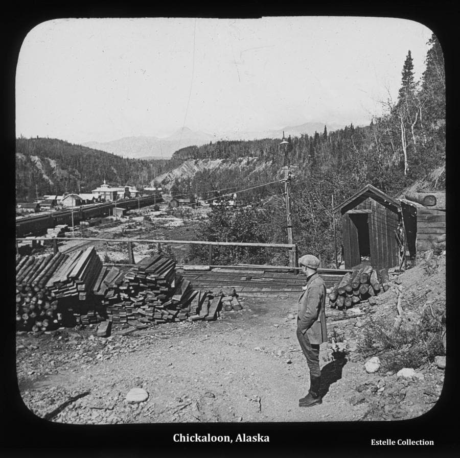 Image shows a man standing in foreground near the mouth of a mine tunnel structure.  Rail tracks used by mine cars accessing the tunnel are evident.  Lumber and logs are stacked nearby.  In middle ground a train with several passenger cars is apparent on the flat land below, as well as numerous large and small buildings.  Power poles are evident near the train and at the mine mouth.  The community is located on the Chickaloon River floodplain with steep bluffs rising on both sides topped with heavy forest.  Mountains are faintly visible in background.