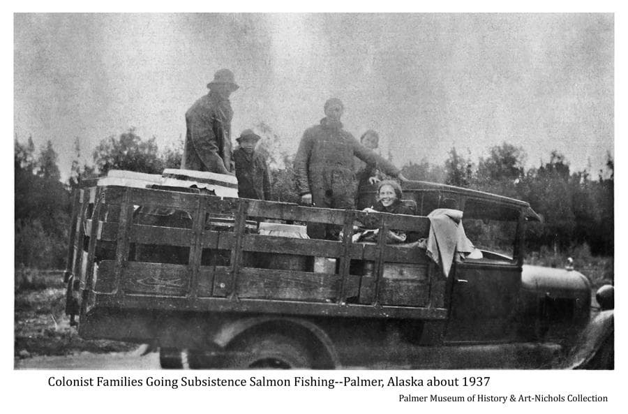 :  Image shows a stake-bed truck with five people in back with barrels and tubs covered with white canvas on their way to gather salmon for the winter.  People are unidentified.  Forest forms the backdrop