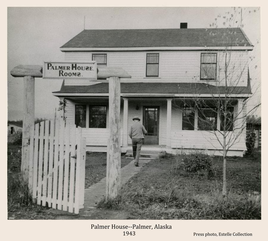 "Image shows a white, two-story house in middle ground with a white picket gate and gate post arch holding a sign ""Palmer House Rooms"" in foreground.  The ""S""s on the sign are printed backwards.  A man is walking on the path towards the house.  Owned by Jim Felton, this was the most available lodging in the local area prior to the coming of the Matanuska Colony.  Rooms reputedly contained two or more beds to accommodate all travelers, typical of Alaska roadhouses in the day."