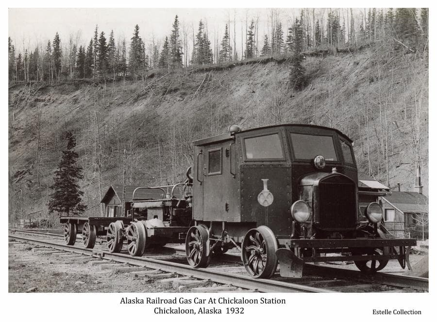 Information associated with this photo identifies it as an Alaska Railroad gas car and two flat trailers on the rails at Chickaloon station in that coal mining community at the north end of the Matanuska branch rail line.  Behind the vehicle are several small buildings at the base of a steep, bare slope topped by trees.