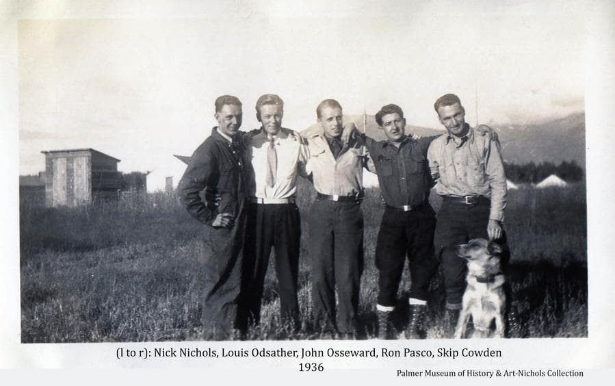 Image shows five men associated with the early colony activity.  They're identified as: (l to r): Clair (Nick) Nichols & Louis Odsather (commissary); John Osseward (ARRC Accountant); Ron Pasco (Railroad Agent); and Skip Cowden (Commissary).  A dog also poses with the men.  A small wooden building and several tents are visible behind the group and mountains are visible in background.