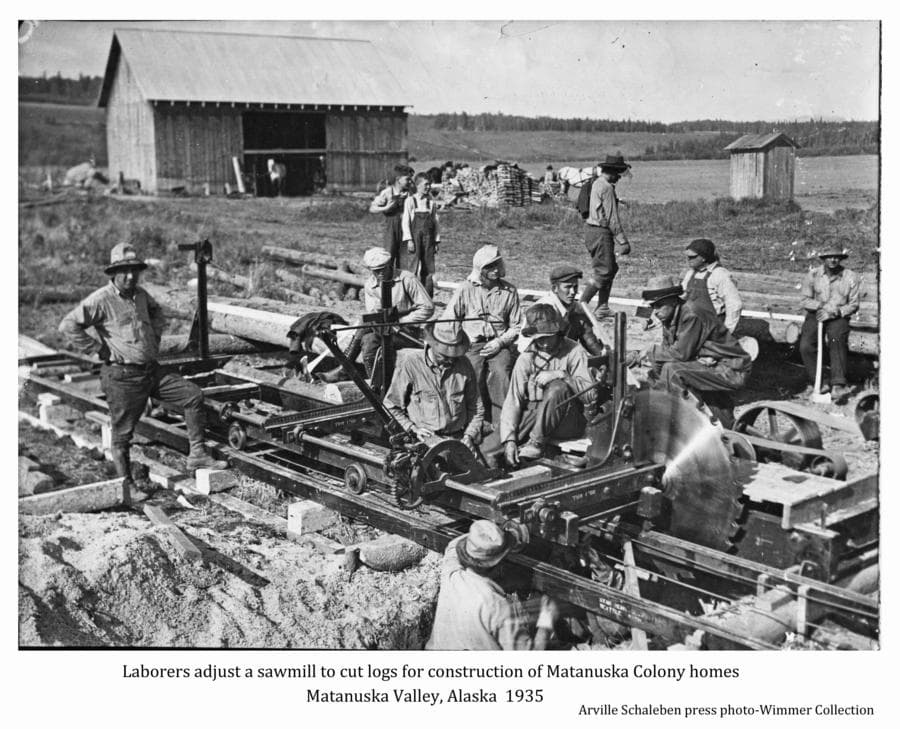 This is a slightly enhanced Milwaukee Journal press photo.  Image shows a group of men gathered around a portable sawmill in foreground.  The mill is temperately shut down in order to adjust the log carriage. Mosquito nets are evident on most hats.  The man third from left is identified as colonist Tom Lepak.  Man in white hood, center, is tentatively identified as colonist Virgil Eckert. Two boys look on.  A homestead barn, woodpile, outhouse and at least two horses are apparent in middle ground.  Cleared fields and forested hills are beyond.  This mill was set up near Camp#2 to saw house logs for constructing Colonist homes in the vicinity of the Matanuska Experiment Farm.