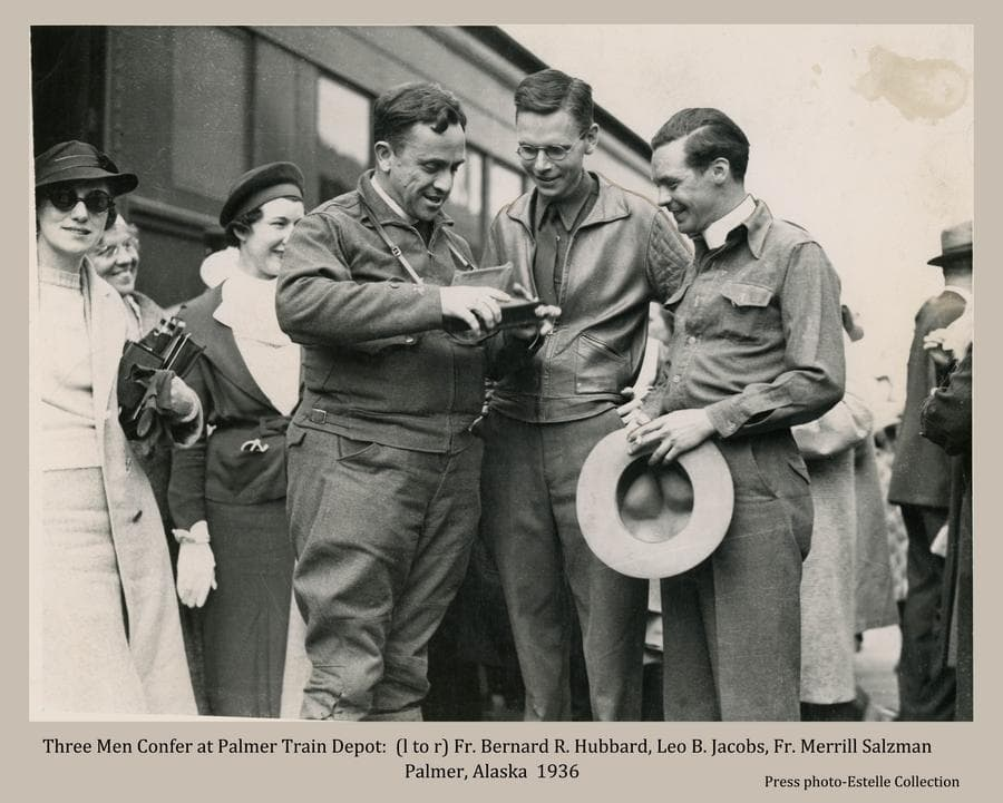 """Image shows three men standing together in foreground looking at something at hand. They are identified as Fr. Bernard R. Hubbard, Leo B. Jacobs, and Fr. Merrill Salzman.  Three women stand next to the men and others are visible beyond.  A train car stands directly behind the people.  Father Hubbard was famously known as the """"Glacier Priest"""", Jacobs was the Colony architect, and Father Salzman was the Catholic priest for Palmer."""