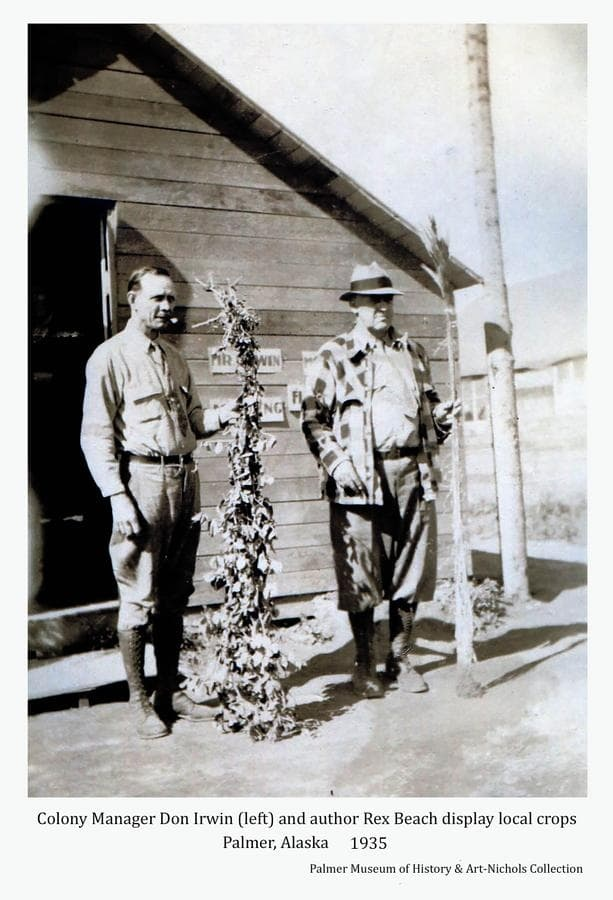Image shows Colony manager Don Irwin and author Rex Beach displaying examples of farm plants presumably produced in the local area.  The men stand in front of a frame building exhibiting signs indicating it was Irwin's office.