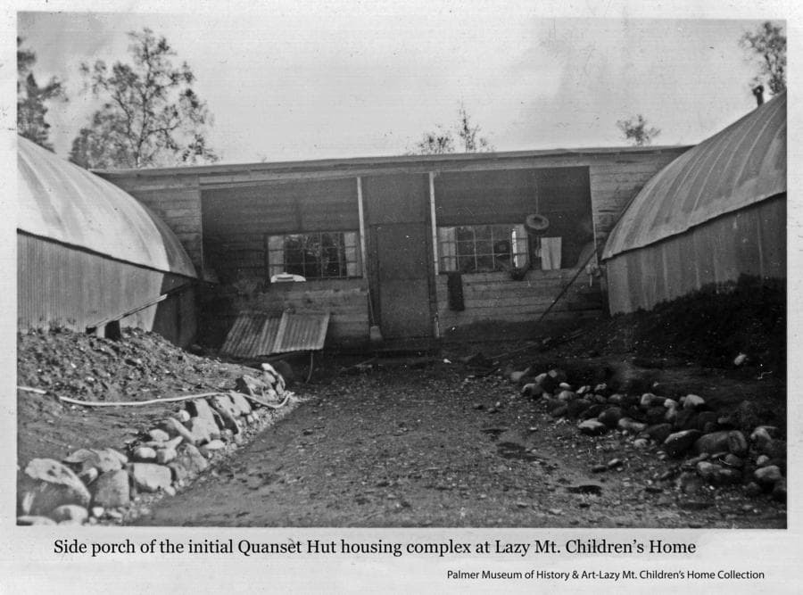 Image is of a rock-line gravel walkway leading to the side porch and doorway of one of the early housing complex buildings at the Children's Home.  Quonset Huts on both sides of the walkway connect to the central building.