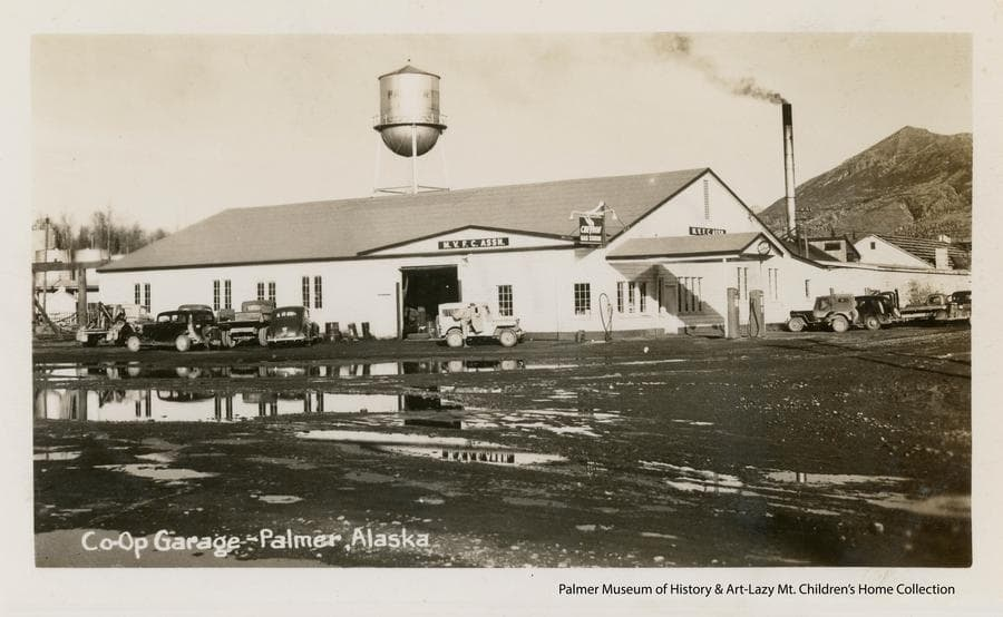 Image shows a large single story building, identified as the Co-op garage, in middle ground with a gravel street and many water puddles in foreground, a variety of automobiles parked in front of the building, and the Palmer water tower above it.  Fuel tanks are visible at the left behind the building.  Gas pumps are apparent at the right of the building, the smokestack from the powerhouse is visible at right and Lazy Mountain is apparent at the far right.