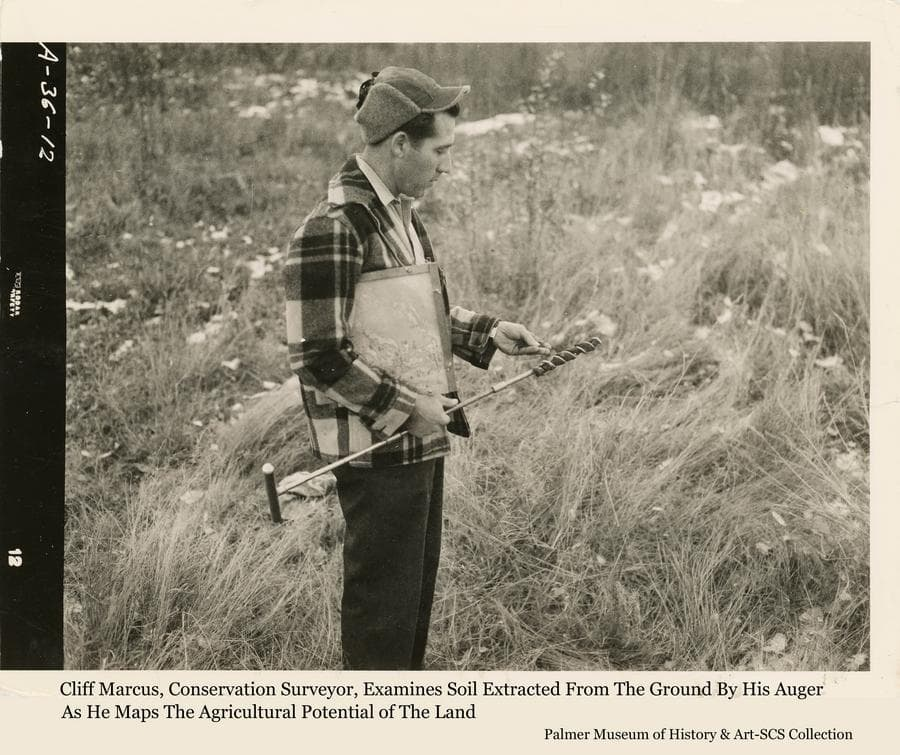Image shows Conservation Surveyor Cliff Marcus, evaluating a soil sample he has extracted with his auger as he maps soil types on the Kenai Peninsula.  Cliff worked out of the State Soil Conservation Service office in Palmer for many years, traveling to various areas of the state to identify and map the soils for their agricultural potential.