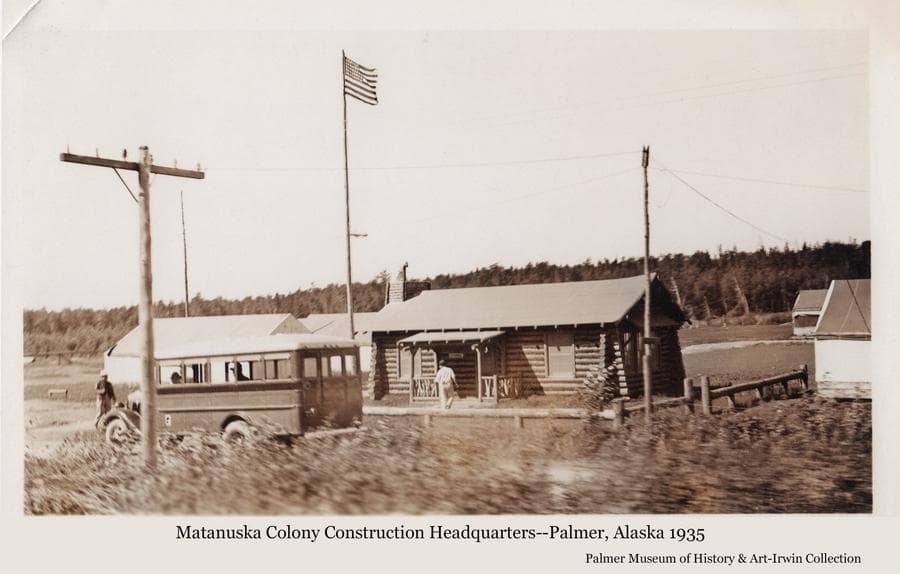 Image shows the first log building constructed by the transient workers employed to build the new buildings associated with the Matanuska Colony.  The building was thought to have been disassembled and reassembled as a training exercise for the workers, and then served as the headquarters for the rest of the construction activities.  A bus is apparent in foreground with two passengers visible inside, two other men are nearby.  A power pole is in foreground and the American flag flies on a tall pole over the building.  Tents are partially visible.  Heavy forest forms a backdrop behind.