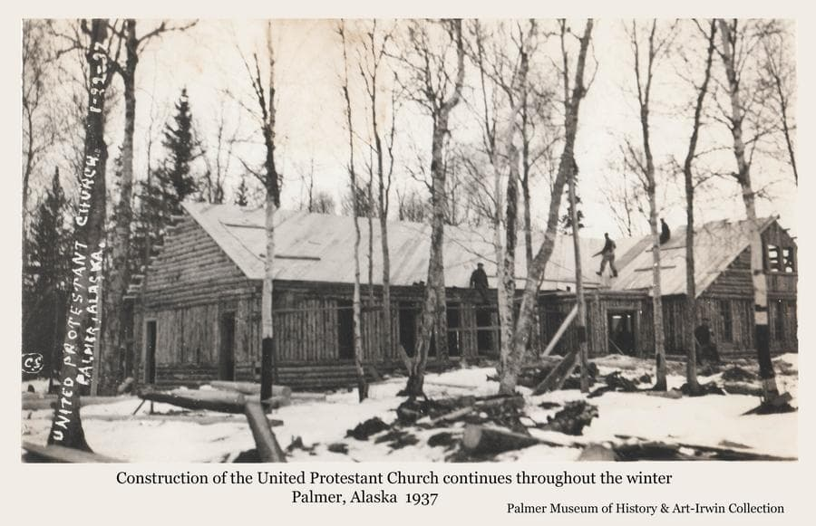 Image is a winter view of the United Protestant Church in Palmer under construction.  Several men are visible applying roof boards on the log structure.  Birch trees are in foreground with snow on the ground.