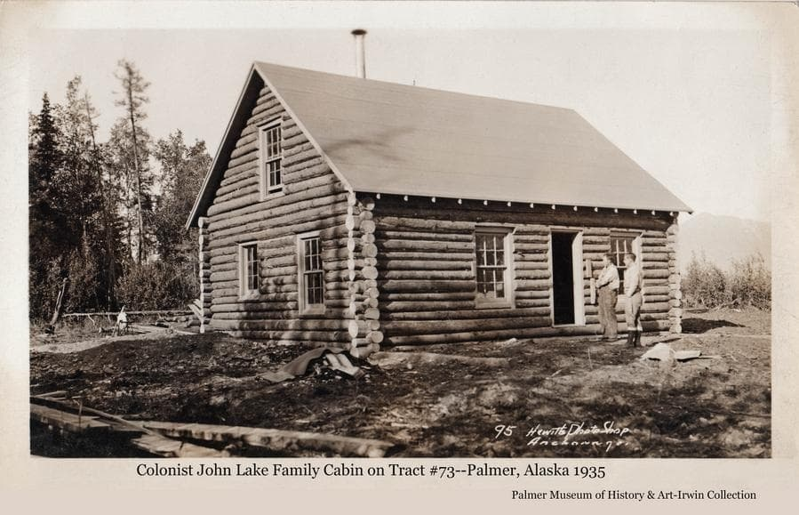 Image is of a log house, identified as belonging to John and Magdalene Lake on tract #73. Two men are standing in front.  Exterior construction appears to be complete with the yard largely cleaned up.  A grindstone is visible behind the house.  Trees are behind at left and Lazy Mountain is faintly visible in background at the right