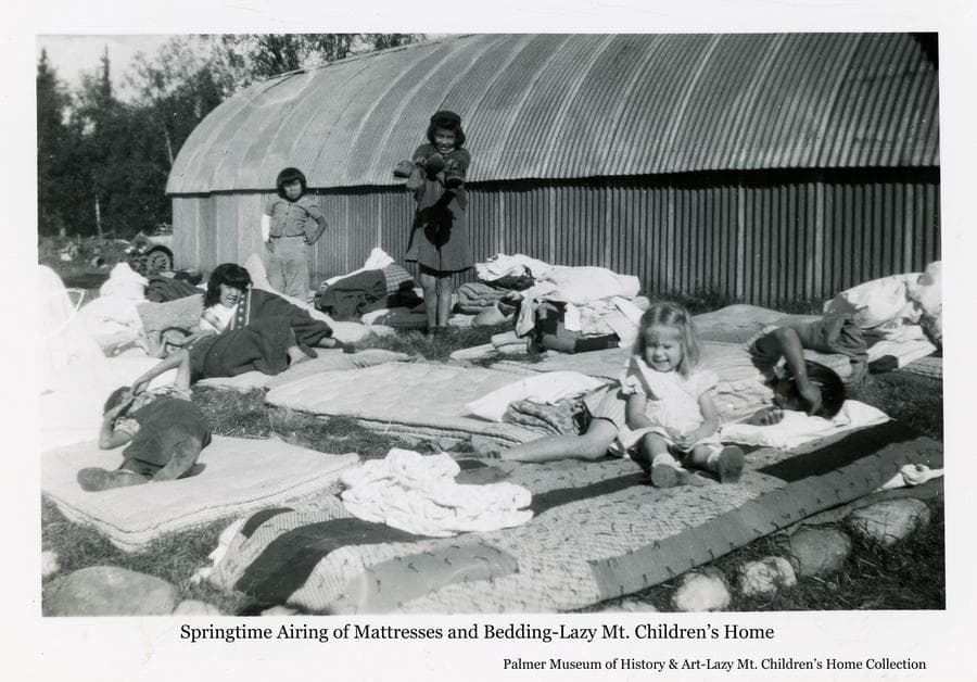 Image is of numerous mattresses and blankets spread on the ground on a sunny day with several children lying and standing on them.  A Quonset Hut is the backdrop.  Trees and the front of the old fire truck are visible beyond at the end of the hut.