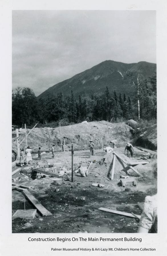 Image shows the excavation for the main building with footings in place, people and lumber on the floor of the excavation.  The well is blocked in at lower left.  Heavy forest in middle ground and Lazy Mountain in background