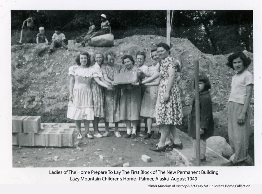 Image shows several women, identified as associated with the Home, holding the first concrete block to be laid in construction of the basement of the new permanent building for the Home.  Several children of the Home look on.