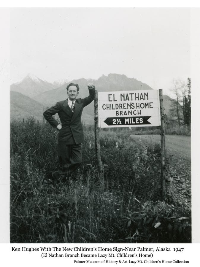 """Image is of Ken Hughes standing beside a sign with directions to the """"El Nathan Children's Home Branch"""", which became the Lazy Mt. Children's Home on Lazy Mountain near Palmer.  Mr. Hughes was the founder and director of the new home.  A road is visible passing the sign with mountains in background."""