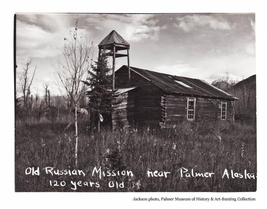 Image is of the old log Russian Orthodox Church at Eklutna.  Scattered trees are visible, other buildings are partially visible beyond the church as are snow-clad mountains.