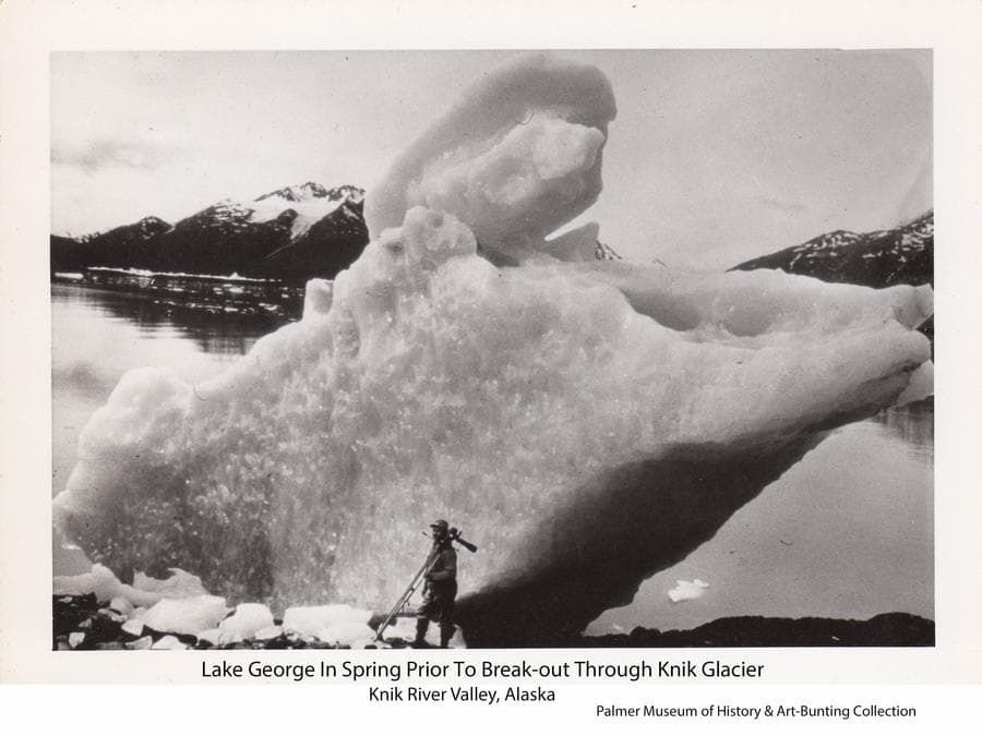 "Image is of a man carrying a tripod and movie camera standing in front of a large iceberg on the shore of a lake, identified as Lake George in the Knik River valley.  Other icebergs are visible in the lake beyond with mountains in background.  The photo was taken while the lake was full of water, prior to its summer break-out through the Knik Glacier.  This glacial lake outburst flood, or ""jokulhlaup"", occurred annually until 1967."