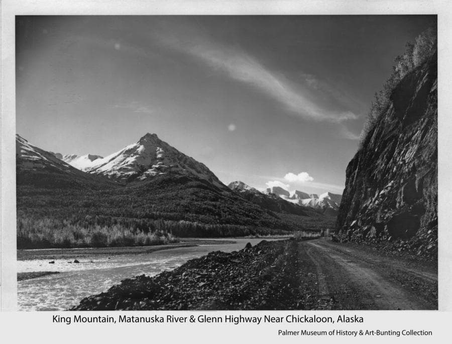 Image shows a shot-rock road, identified as Glenn Highway, with a steep rock cliff at the right and the Matanuska River running parallel at the left.  A conical-shaped snow-clad mountain, identified as King Mountain, is prominent in middle ground with heavily forested foothills.  Other snow-clad mountains are visible in background.