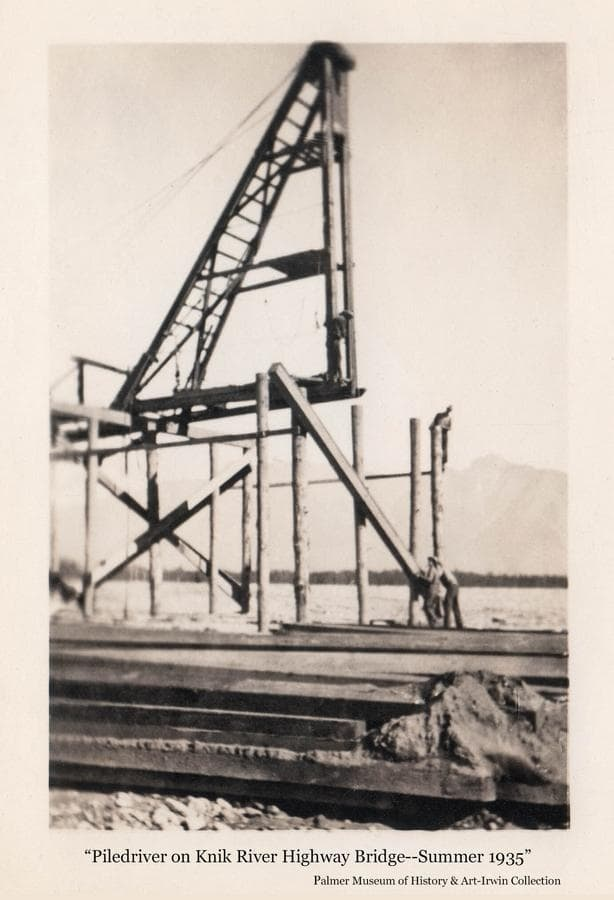 Image shows a summer view of men operating a pile driver placing timbers for construction of a highway bridge over the Knik River to connect the road between Palmer and Anchorage.