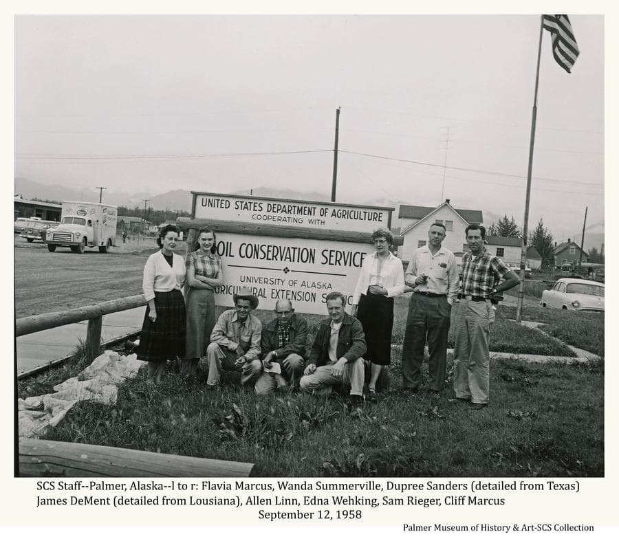 Image shows the Soil Conservation staff at Palmer during the summer of 1958 posing in front of the Palmer office.  Identified as (l to r): Flavia Marcus, Wanda Somerville, Dupree Sanders (detailed from Texas), James DeMent (detailed from Louisiana), Allan Linn, Edna Wehking, Sam Rieger, Cliff Marcus.  Not shown is Charles Willson who took the picture.  The two detailers were here for the season to conduct soil surveys.